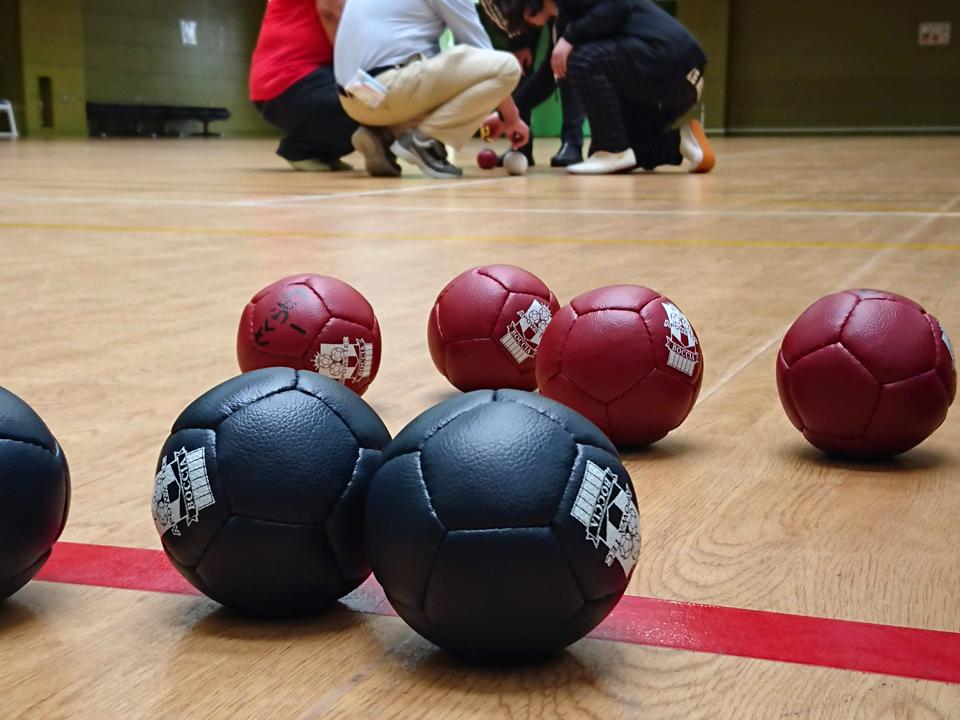 ボッチャのボールの距離を判定する皆さんの写真
